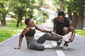 Caring Black Man Massaging Injured Leg Of Girlfriend After Running Together Outdoors