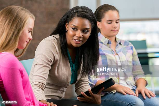 Caring counselor talks with teenage girl about social issues