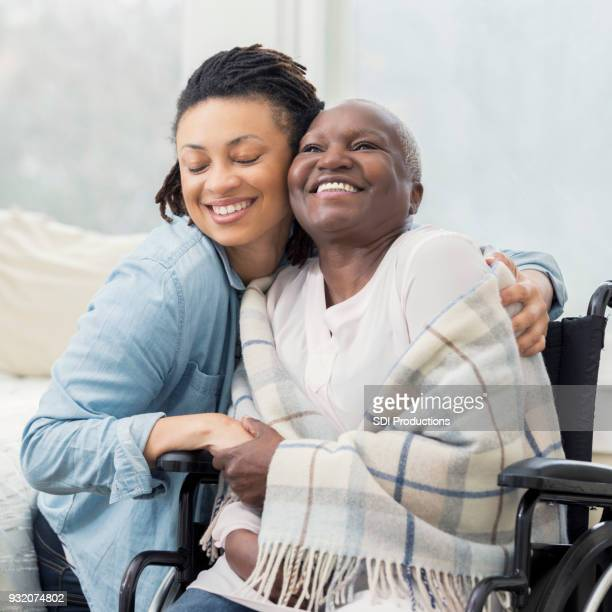 caring daughter hugs wheelchair-bound mother - black square stock pictures, royalty-free photos & images
