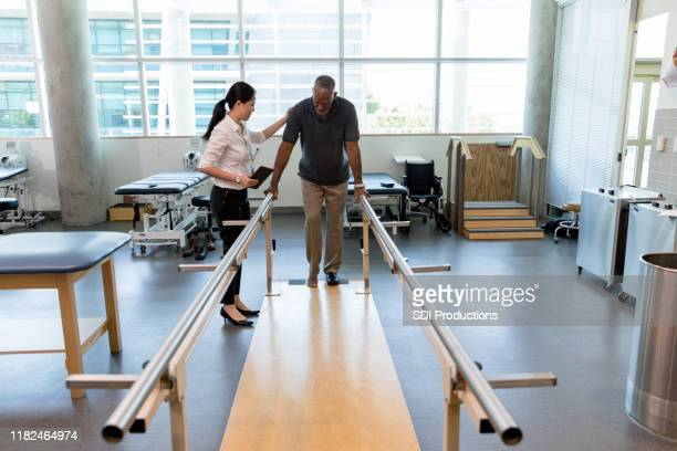 caring female physical therapist helps stroke victim in rehab center - recovery stock pictures, royalty-free photos & images
