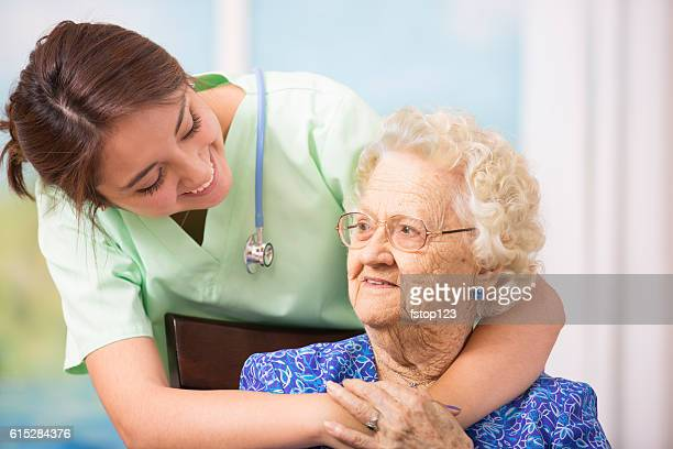 Caring, hispanic nurse and senior patient at nursing home.