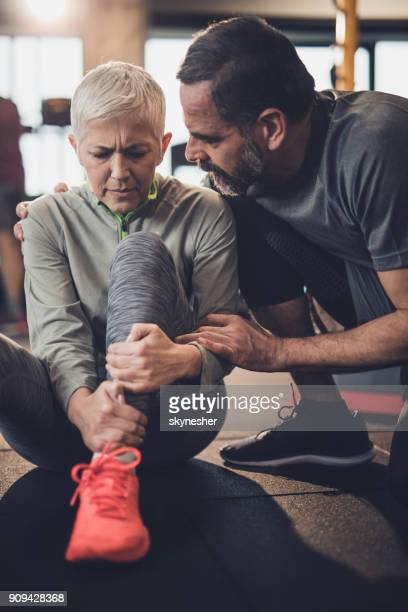 caring husband helping his injured wife in a health club. - knees together stock photos and pictures