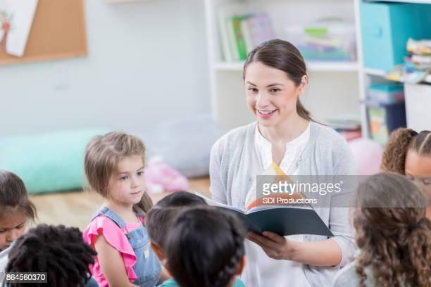 carinhosa educadora lê o livro de história, a classe - literatura - fotografias e filmes do acervo