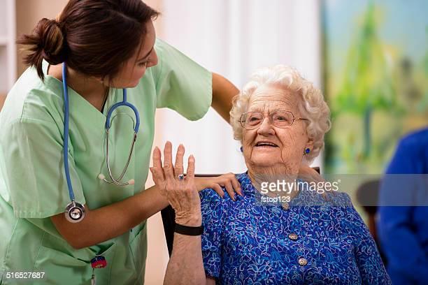 Caring Latin descent nurse talks with her elderly patient.