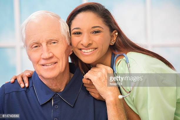 Caring, mixed-race nurse and senior adult patient in hospital.