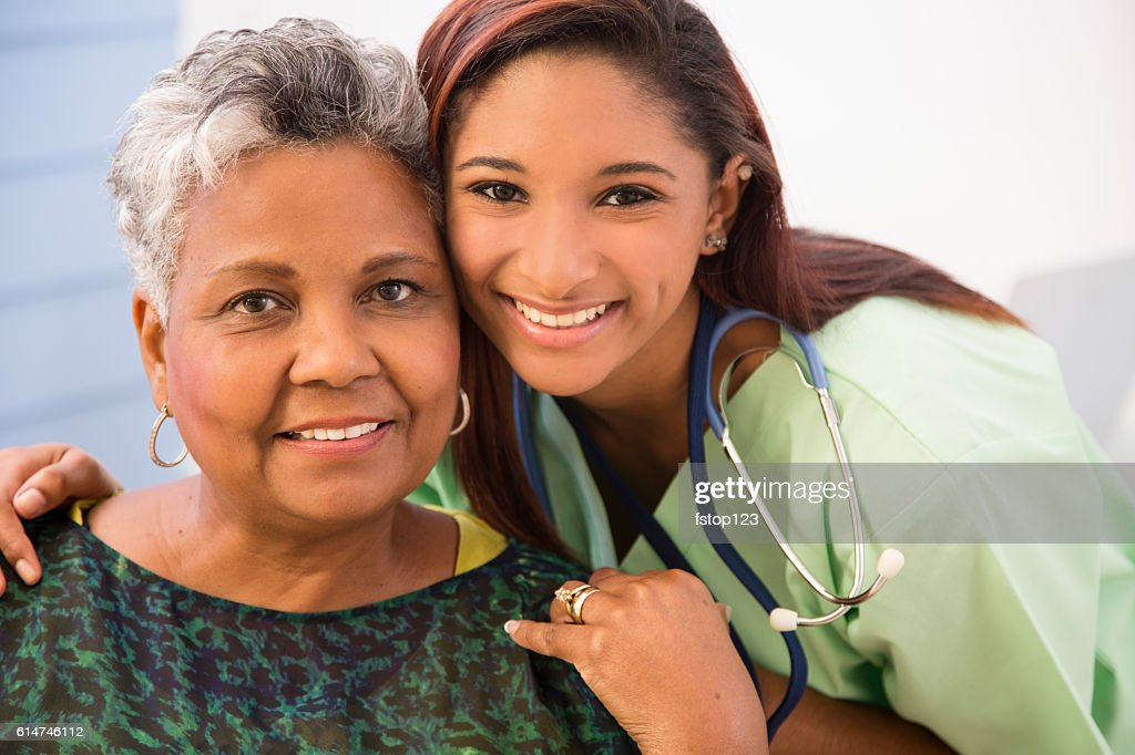 Caring, mixed-race nurse and senior adult patient in hospital. : Stock Photo