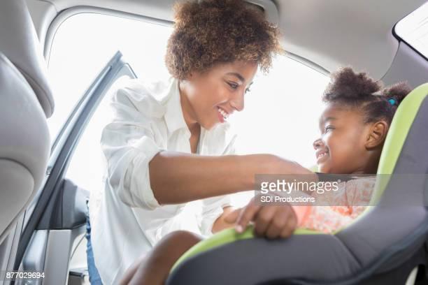 思いやりのあるママは、車の座席に娘を慎重にストラップ