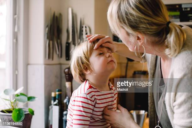 caring mother looking at daughter's bruised eye in kitchen - plaie photos et images de collection