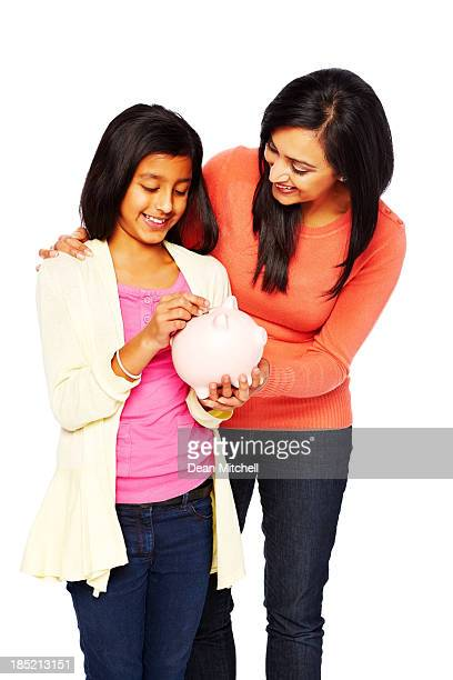Caring mother teaching her daughter to save money