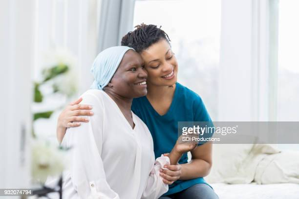 Caring nurse comforts elderly female patient