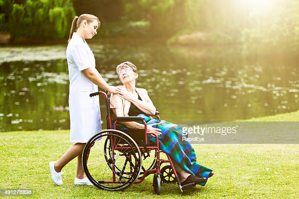 Caring nurse shares affectionate moment with old woman in wheelchair