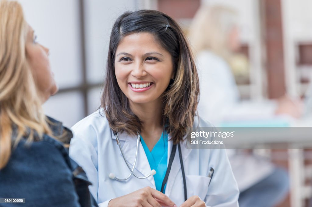 Caring physician talks with female patient : Stock Photo