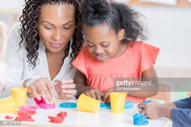 Caring preschool teacher helps girl with molding clay