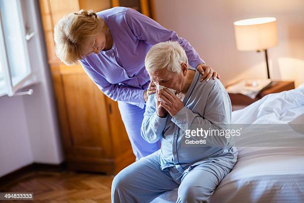 Caring senior woman taking care of her husband