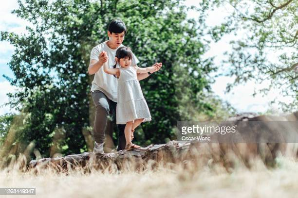 caring young asian father holding hands of his little daughter and assisting her to walk along a tree trunk outdoor on a sunny day - active lifestyle stock pictures, royalty-free photos & images