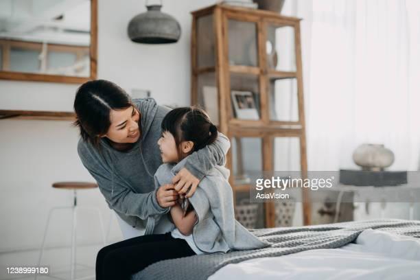 jeune mère asiatique de soins mettant un manteau sur sa fille à la maison - protection photos et images de collection