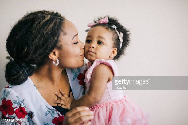 caring young mother and her one year old baby girl having fun together. - pink dress stock pictures, royalty-free photos & images