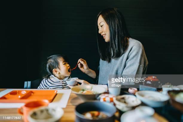 caring young mother feeding cute little daughter while enjoying delicate japanese cuisine in restaurant - washoku fotografías e imágenes de stock