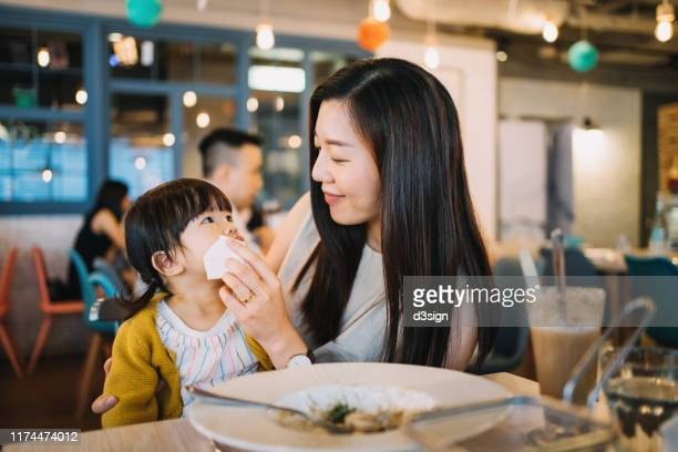 caring young mother wiping daughter's mouth after meal in a restaurant - ティッシュ ストックフォトと画像