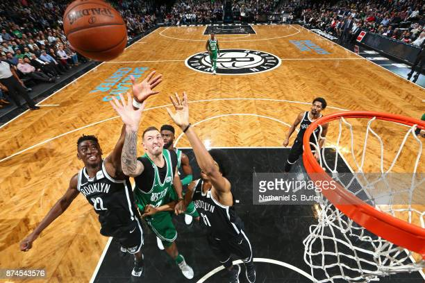 Caris LeVert of the Brooklyn Nets and Daniel Theis of the Boston Celtics go up for a rebound on November 14 2017 at Barclays Center in Brooklyn New...