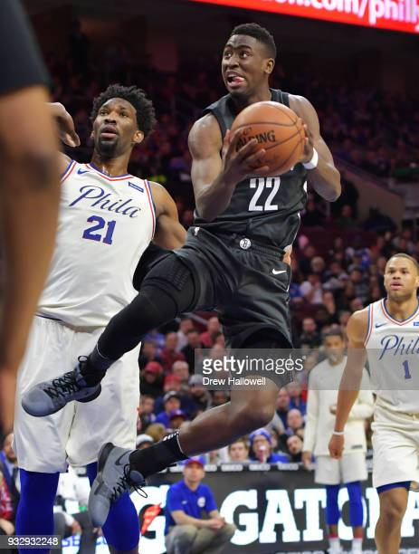Caris LeVert of the Brooklyn Nets lays up a shot in front of Joel Embiid of the Philadelphia 76ers at the Wells Fargo Center on March 16 2018 in...