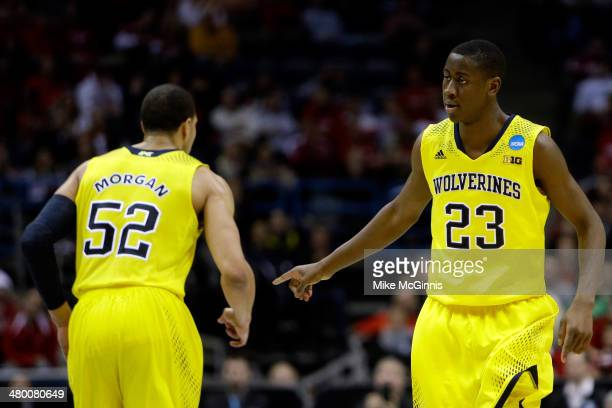 Caris LeVert of the Michigan Wolverines celebrates with teammate Jordan Morgan after making a three point shot in the second half against the Texas...