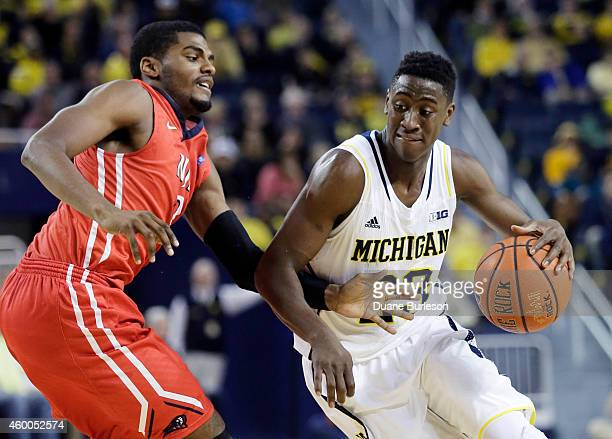 Caris LeVert of the Michigan Wolverines drives to the basket against Tim Coleman of the New Jersey Institute of Technology Highlanders during the...