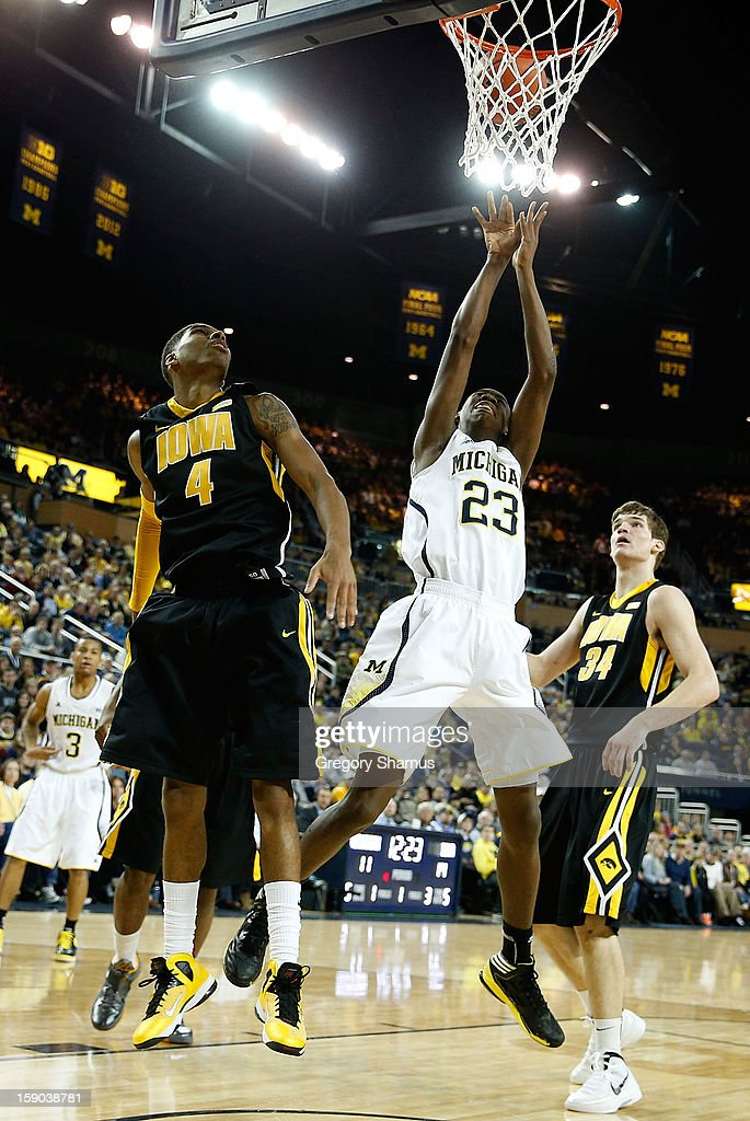 Caris LeVert #23 of the Michigan Wolverines gets off a first half shot next to Roy Devyn Marble #4 of the Iowa Hawkeyes at Crisler Center on January 6, 2013 in Ann Arbor, Michigan. Michigan won the game 95-67.
