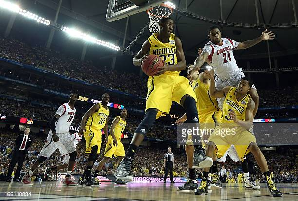 Caris LeVert of the Michigan Wolverines looks to pass against Chane Behanan of the Louisville Cardinals during the 2013 NCAA Men's Final Four...