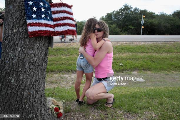 Carissa Potts hugs her 7yearold daughter Kaylee after leaving flowers at a small memorial outside of Santa Fe High School on May 19 2018 in Santa Fe...