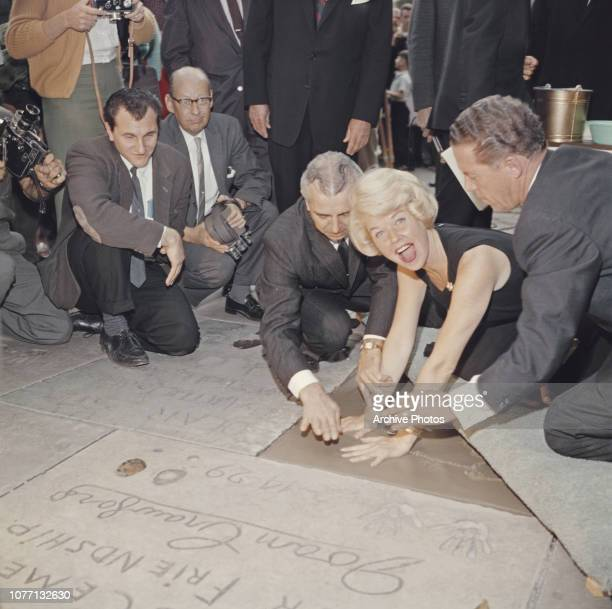 Carl Anderson helps American actress and singer Doris Day plants her handprints in cement outside Grauman's Chinese Theatre, Hollywood, California,...