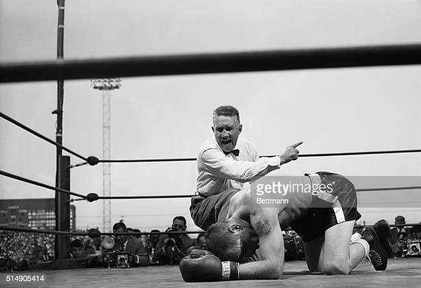 "Carl ""Bobo"" Olson is counted out by referee Mushy Callahan after being knocked out by Sugar Ray Robinson in the fourth round of their world..."