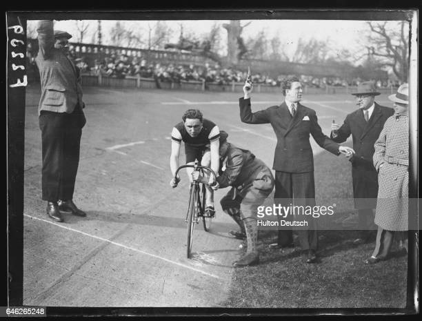 Carl Brisson, the actor, prepares to fire the starter's pistol for the Great Olympic Revenge race between cyclists Henry Hansen and F.W. Southall.