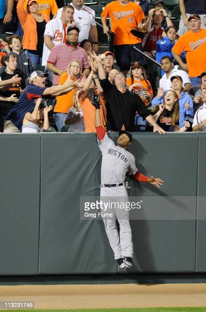 Carl Crawford of the Boston Red Sox tries to catch a home run by Adam Jones of the Baltimore Orioles in the fourth inning at Oriole Park at Camden...