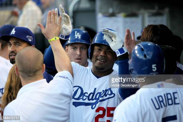 Carl Crawford of the Los Angeles Dodgers celebrates in the dugout after he hits a threerun home run in the second inning against the Atlanta Braves...