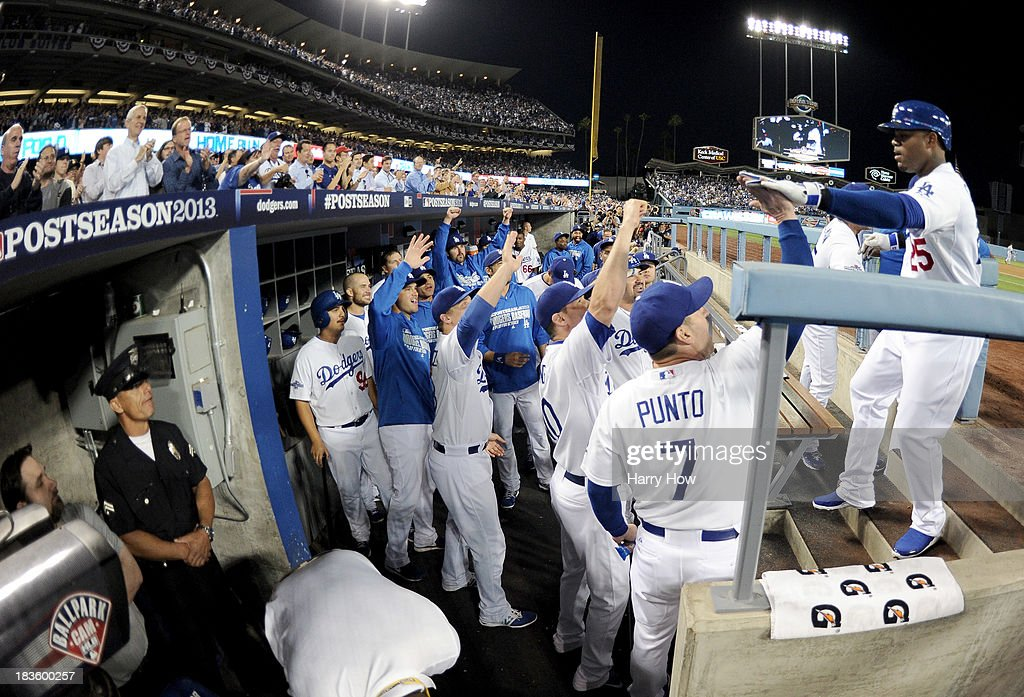 Carl Crawford #25 of the Los Angeles Dodgers celebrates with teammates at the dugout steps after he hits a first inning home run against the Atlanta Braves in Game Four of the National League Division Series at Dodger Stadium on October 7, 2013 in Los Angeles, California.