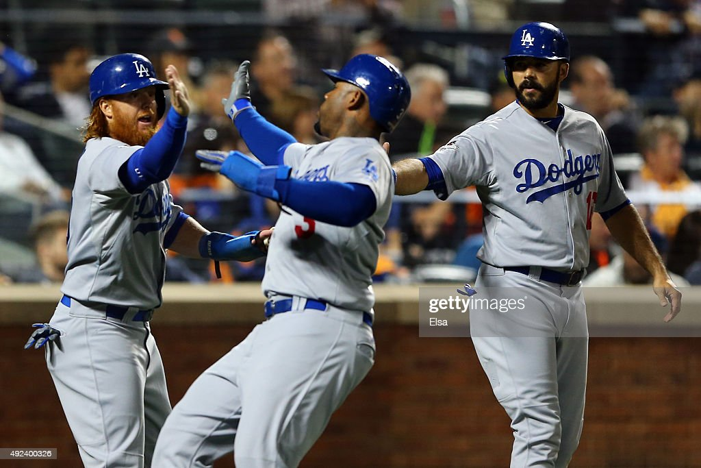 Carl Crawford #3 of the Los Angeles Dodgers celebrates with teammates Andre Ethier #16 and Justin Turner #10 after scoring off of Yasmani Grandal #9 single to right field in the second inning against Matt Harvey #33 of the New York Mets during game three of the National League Division Series at Citi Field on October 12, 2015 in New York City.