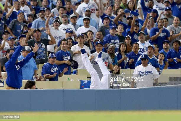 Carl Crawford of the Los Angeles Dodgers makes a catch on a ball hit by Brian McCann of the Atlanta Braves and falls into the stands in the eighth...