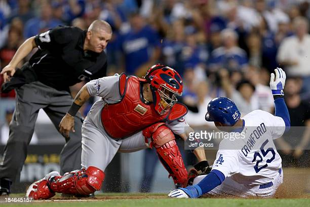 Carl Crawford of the Los Angeles Dodgers slides safely under the tag of Yadier Molina of the St Louis Cardinals as he scores a run in the eighth...