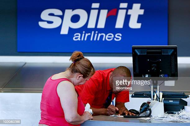 Carl Crawley, right, helps re-book passenger Aurea Comas on a flight to San Juan, Puerto Rico, at the Spirit Airlines counter at Detroit-Wayne County...