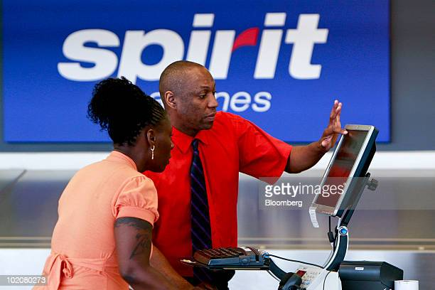 Carl Crawley, right, helps re-book passenger Vanessa Morris on a flight to New York at the Spirit Airlines counter at Detroit-Wayne County...