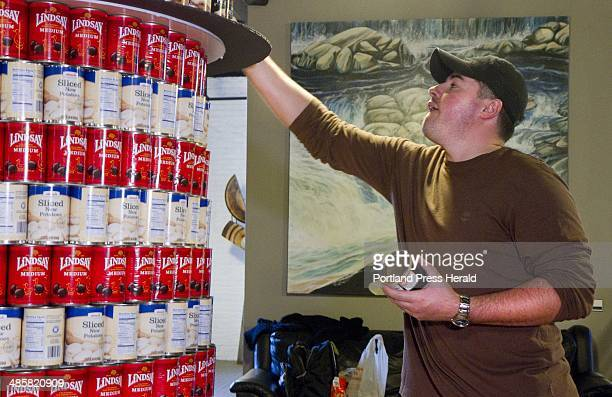 Jonah DeWaters of Oak Point Associates of Biddeford constructs a replica of West Quoddy Head Light out of cans during a Canstruction competition in...
