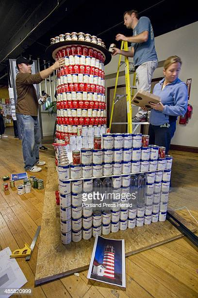 Members of Oak Point Associates of Biddeford construct a replica of West Quoddy Head Light out of cans during a Canstruction competition in downtown...