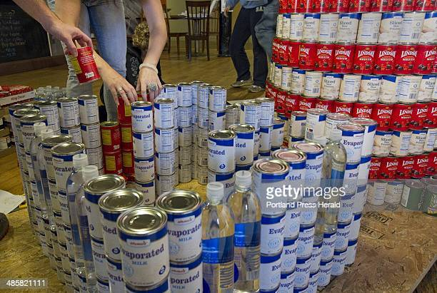 Members of the Oak Point Associates of Biddeford construct a replica of West Quoddy Head Light out of cans during a Canstruction competition in...