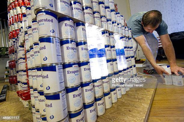 Nick DeFries of Oak Point Associates of Biddeford constructs a replica of West Quoddy Head Light out of cans during a Canstruction competition in...