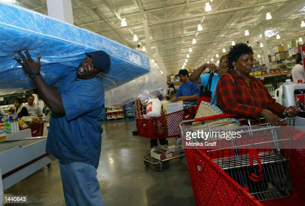 Carl Daniels of Brooklyn hoists a matress onto his shoulder as he waits in line at BJ's Warehouse October 1 2002 at the Gateway Center in Brooklyn...