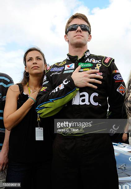 Carl Edwards driver of the Aflac Ford and wife Kate Edwards cover their heart during the singing of the national anthem as they stand next to his car...