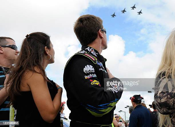 Carl Edwards driver of the Aflac Ford and wife Kate Edwards watch a fly over during the singing of the national anthem as they stand next to his car...