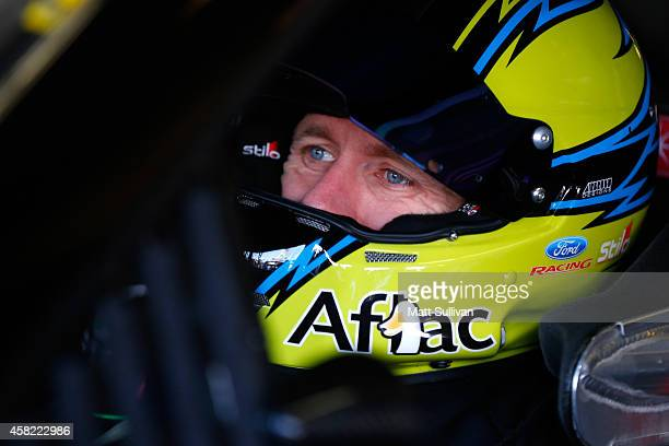 Carl Edwards, driver of the Aflac Ford, sits in his car in the garage area during practice for the NASCAR Sprint Cup Series AAA Texas 500 at Texas...