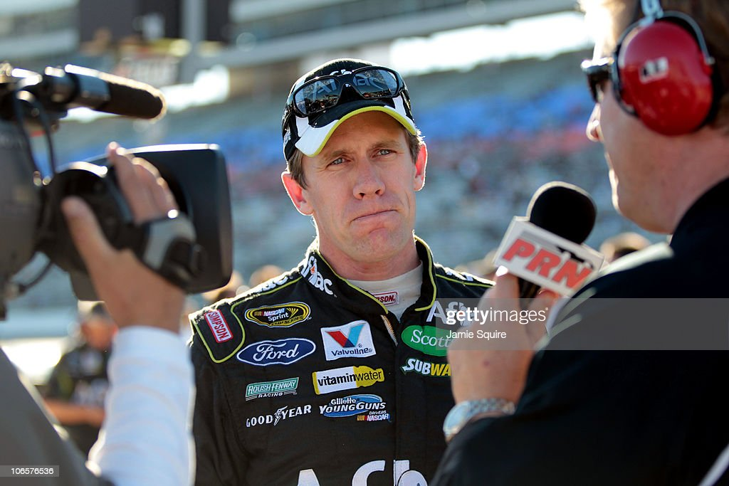 Carl Edwards (C), driver of the #99 Aflac Ford, speaks to the media after qualifying for the NASCAR Sprint Cup Series AAA Texas 500 at Texas Motor Speedway on November 5, 2010 in Fort Worth, Texas.